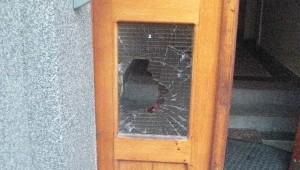 Rozbité dveře bytového domu, všude byly patrné stopy krve